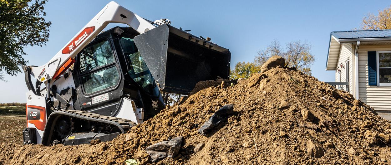 A Bobcat T66 Compact Track Loader Dumping Dirt Into a Pile