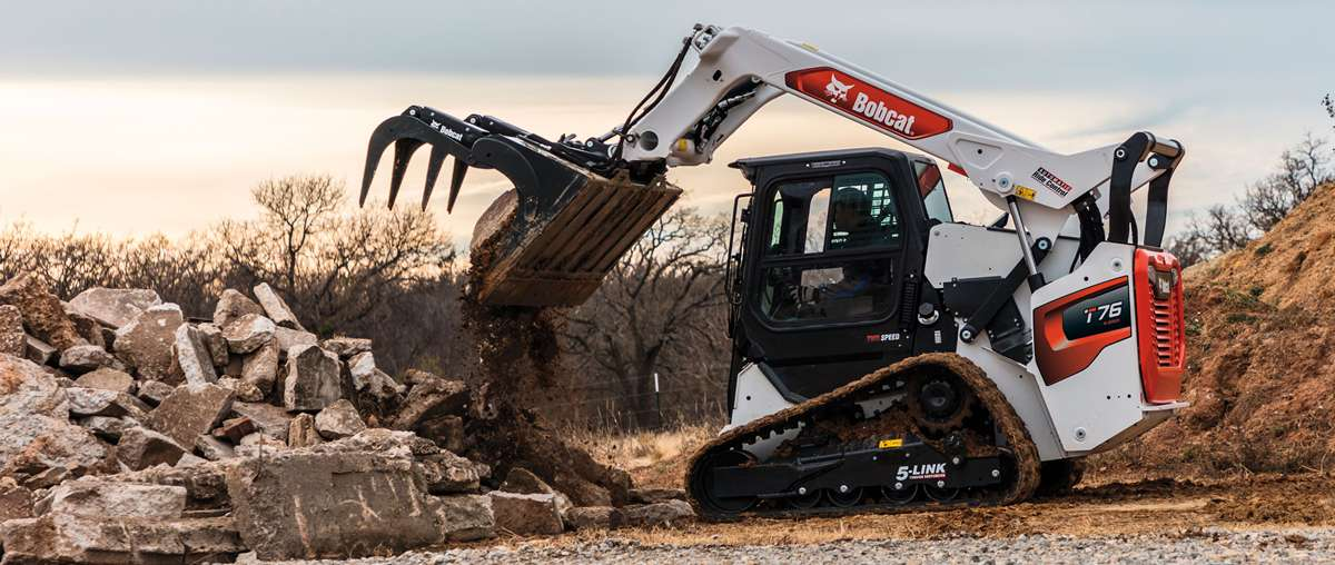 A Bobcat T76 Compact Track Loader Dumping Debris With a Grapple Attachment