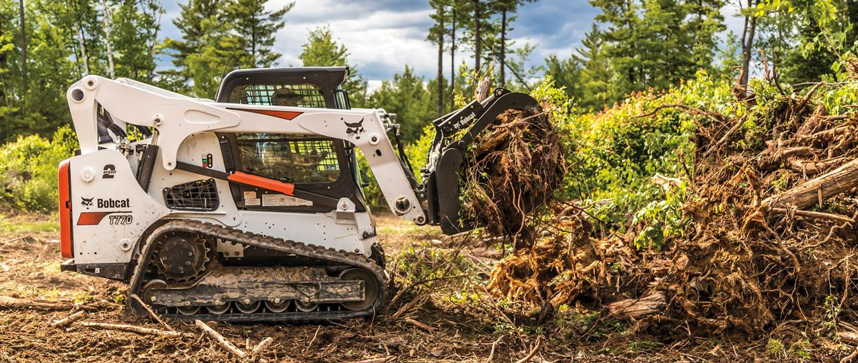 A Bobcat T770 Compact Track Loader Removing Brush With a Root Grapple