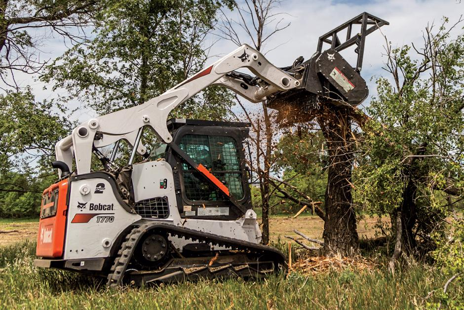 Landscaper Operating T870 Compact Track Loader With Forestry Cutter Attachment To Cut Through Tree