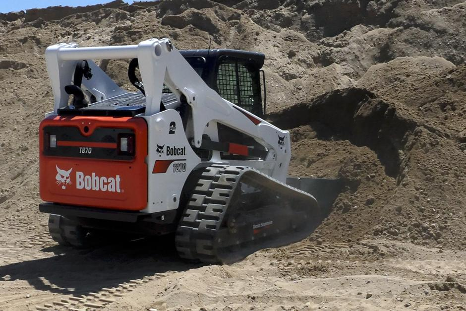 Bobcat T870 compact track loader with 5-Link torsion suspension undercarriage pushes into a pile in video.