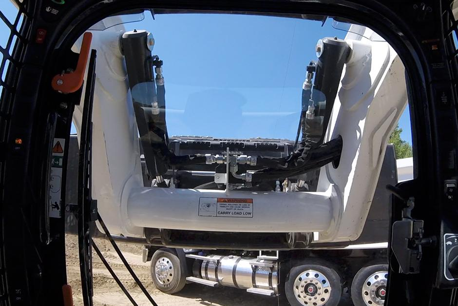 Video from inside a compact track loader as it lifts material into a high-sided truck.
