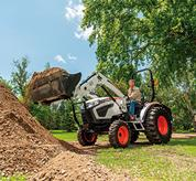 Front-End Loader on a Bobcat Compact Tractor Lifting Dirt on Acreage
