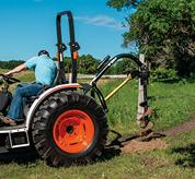 Compact Tractors with Independent Power Take-Off Drilling a Post on a Farm