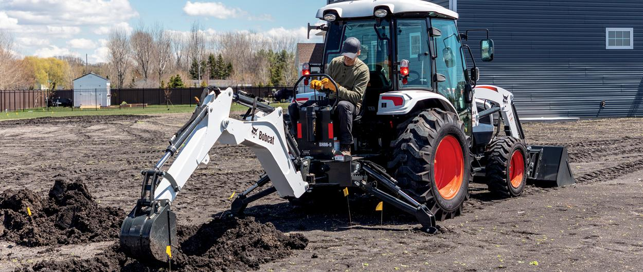 Landscaper Using A Bobcat Compact Tractor With Backhoe Implement To Dig In Yard