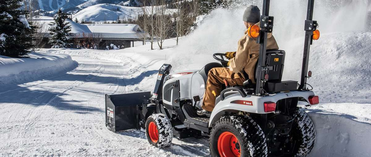 Compact tractor uses a snowblower to move snow