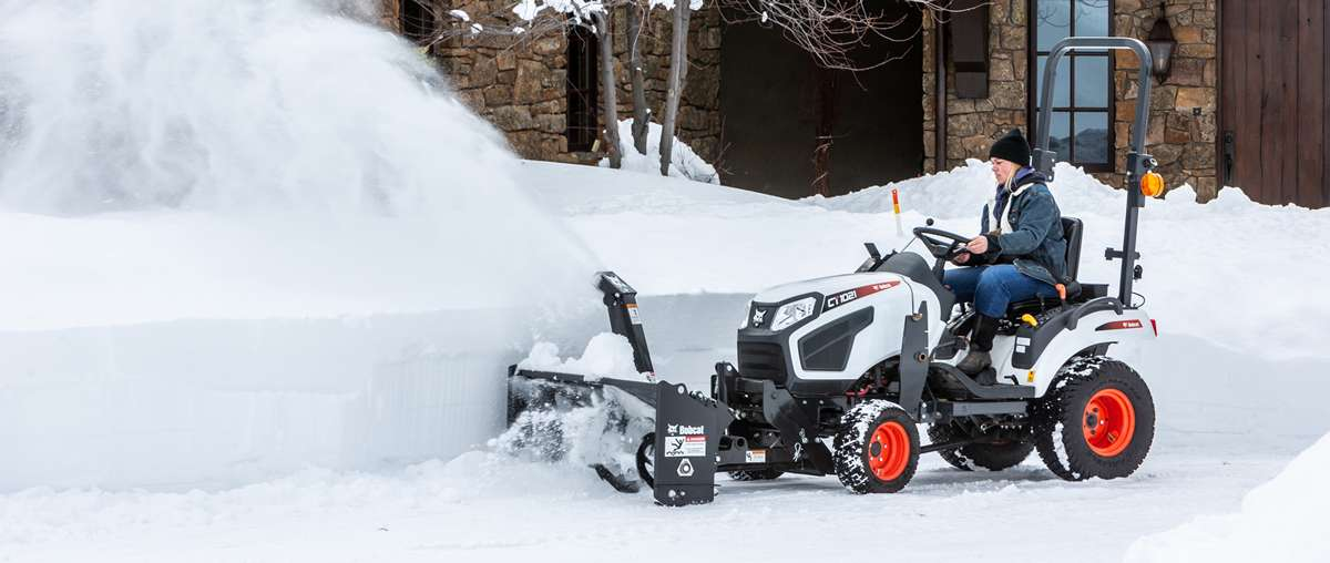 Homeowner Using A Snowblower To Move Snow On A Bobcat Compact Tractor.