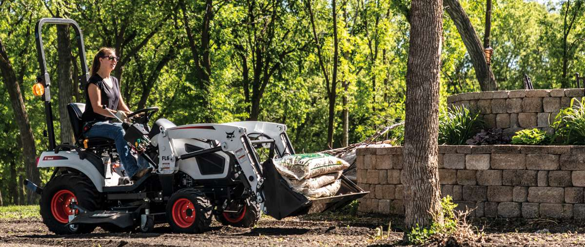 Compact Tractor Operator Carries Bags of Mulch With a Front-End Loader