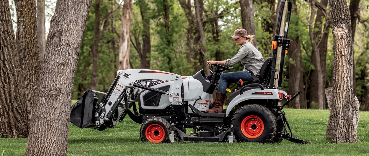 Operator Mowing Between And Around Trees With A CT1025 Compact Tractor and Mid-Mount Mower Attachment