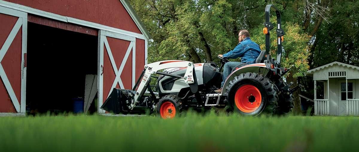 Farmer Driving Compact Tractor Into Barn on Acreage