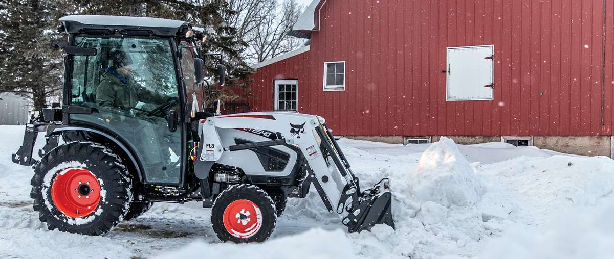 Compact Tractor Operator Using a Front-end Loader to Get Work Done