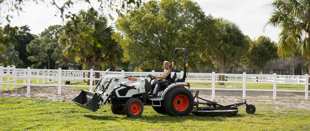 Bobcat tractor owner, Jodi D'Amico, seated on her CT2040 with front-end loader and 3-point rotary cutter.