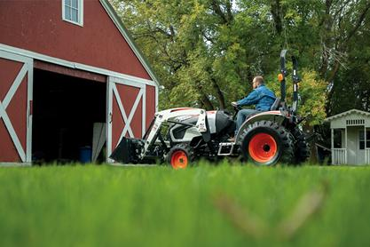 Operator Driving A Bobcat CT2025 Compact Tractor Into His Barn In Rural Setting