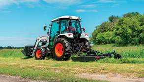 Bobcat Compact Tractor With Front-End Loader Attachment and Finish Mower Implement In a Field