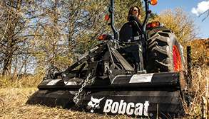 Landowner Using Bobcat CT4058 Compact Tractor With Three-Point Tiller Attachment To Cultivate Soil On Acreage