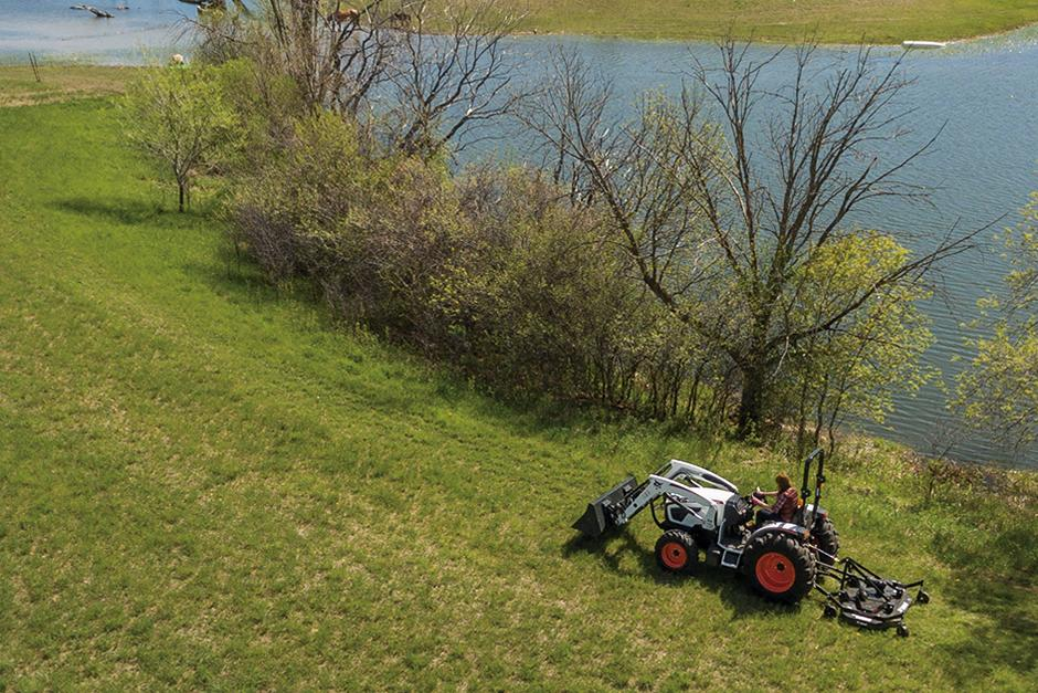 Aerial Shot Of Operator Using Bobcat CT4050 Compact Tractor With Three-Point Finish Mower To Mow Grass Along Pond
