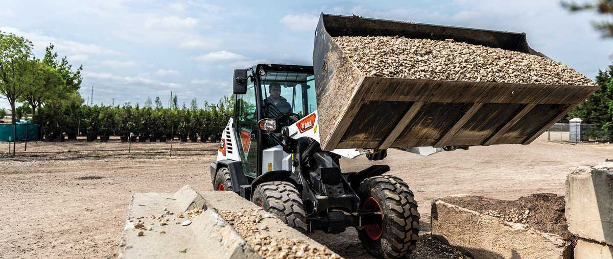 Bobcat Compact Wheel Loader With Bucket Attachment Dumping Rock Into A Pile At A Jobsite.