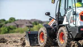 A compact wheel loader pushes dirt along the ground as it travels away.