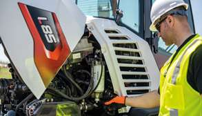 A worker performs maintenance on a compact wheel loader via its open rear service compartment.