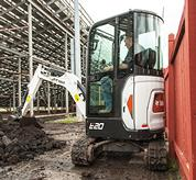 Bobcat E20 compact (mini) excavator working in a tight area of a jobsite.