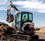 Bobcat E35 compact (mini) excavator positioning a bucket attachment over a dirt pile.