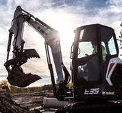 Bobcat E35 compact (mini) excavator lifting a load of black dirt.
