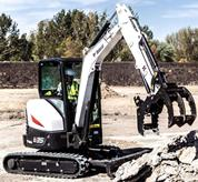 Bobcat compact (mini) excavator positioning the grapple attachment to move debris.