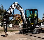 Bobcat (mini) excavator drilling into the ground.