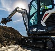 Bobcat E35 compact (mini) excavator digging into a dirt pile with a bucket and clamp attachment.