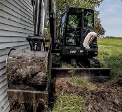 Operator Using E60 Compact Excavator With Bucket Attachment To Dig Trench Next To Home