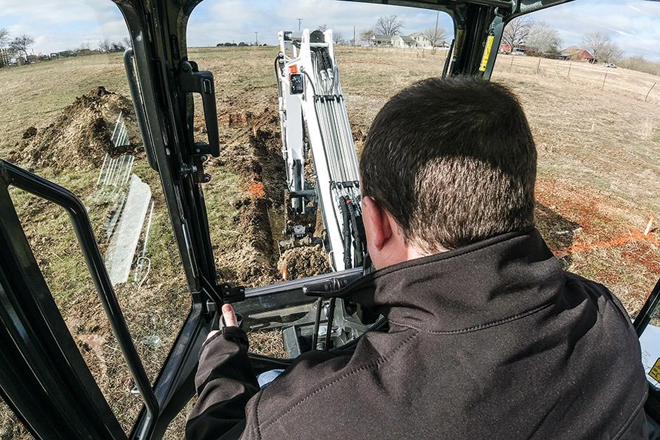 Operator Digs A Trench In A Field With A Bobcat Mini Excavator