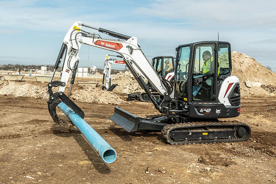 Utility Workers Using Bobcat R2-Series Mini Excavators With Grapple Attachments To Lay Pipe