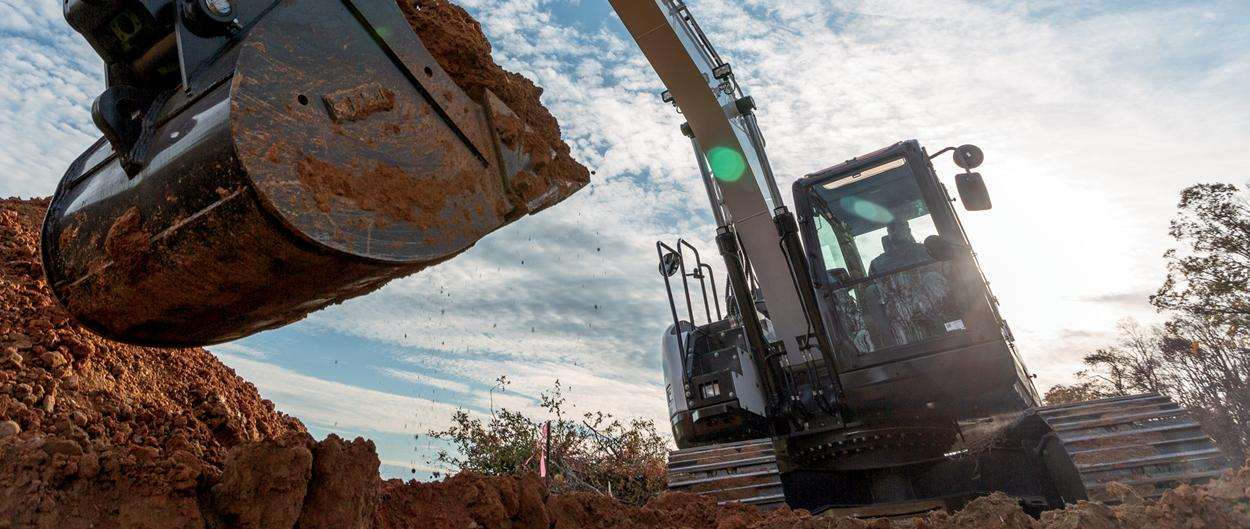 Worker Using A Bobcat E145 Large Excavator With Bucket Attachment To Lift Dirt