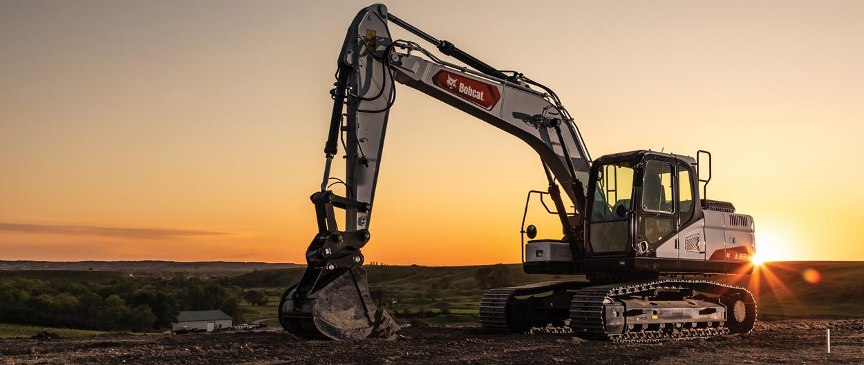 An E165 Excavator Is Positioned in Front of the Setting Sun