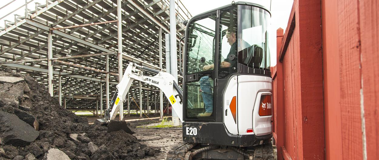 Bobcat compact excavator (mini excavator) works next to fence.