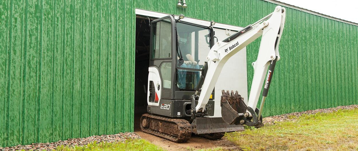 Bobcat E20 compact (mini) excavator with retractable undercarriage driving through small doorway.