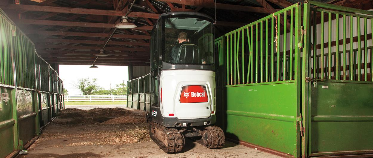 Bobcat E20 compact (mini) excavator with zero tail swing working in a barn.