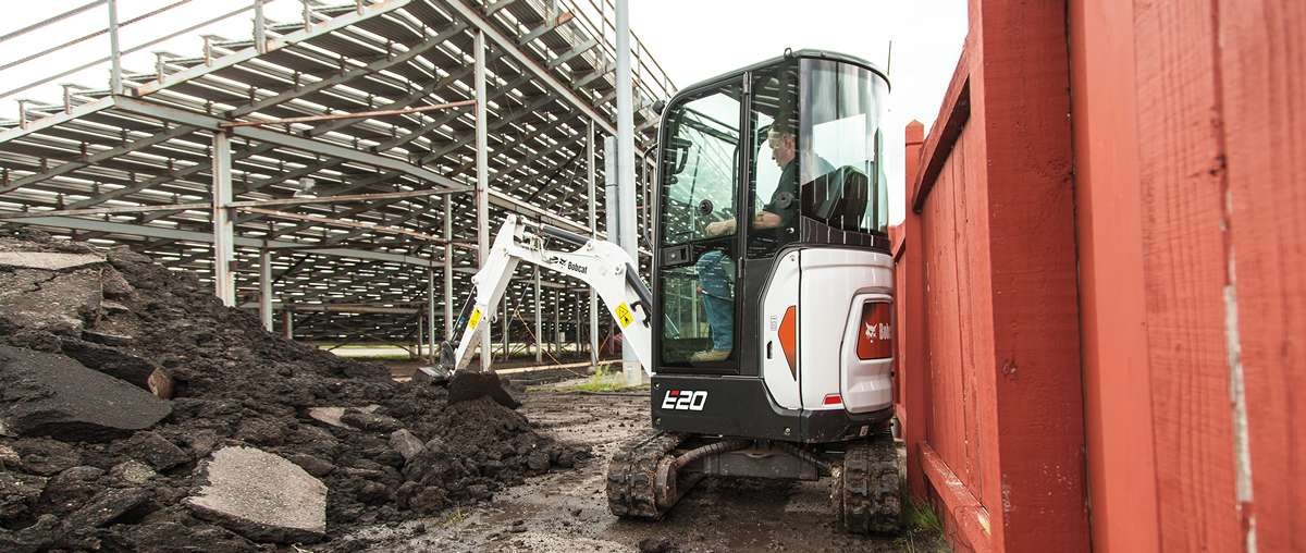 Bobcat E20 compact (mini) excavator with zero tail swing moving dirt on a jobsite.