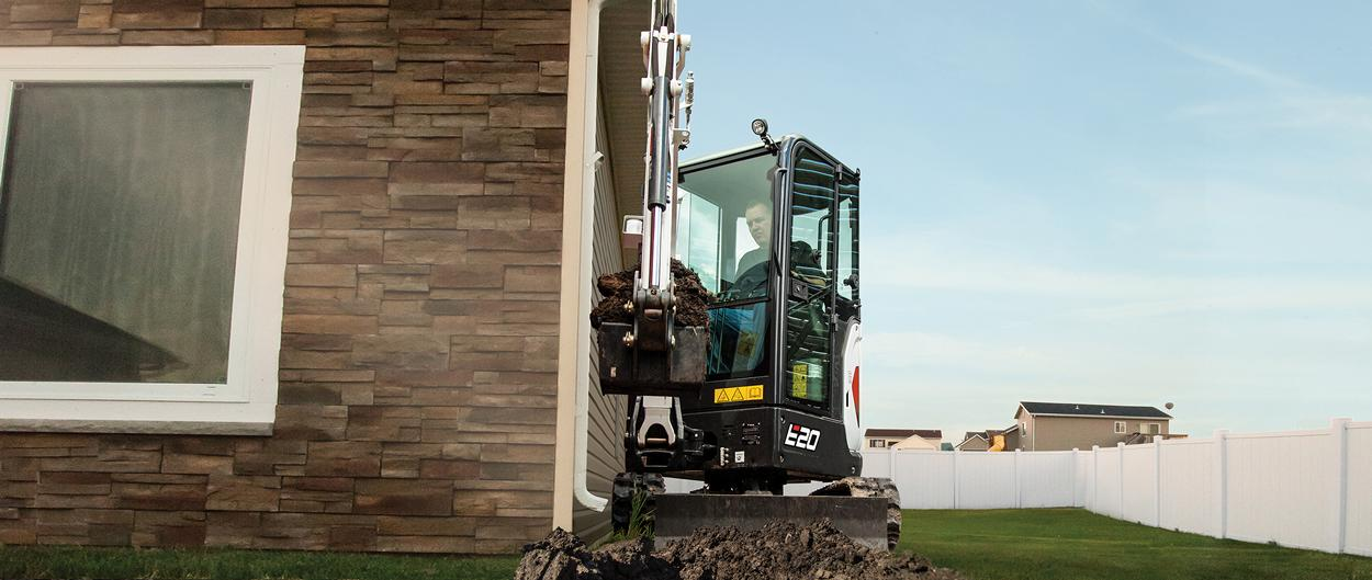 Bobcat E20 compact (mini) excavator with top-mounted boom cylinder working on a house foundation.