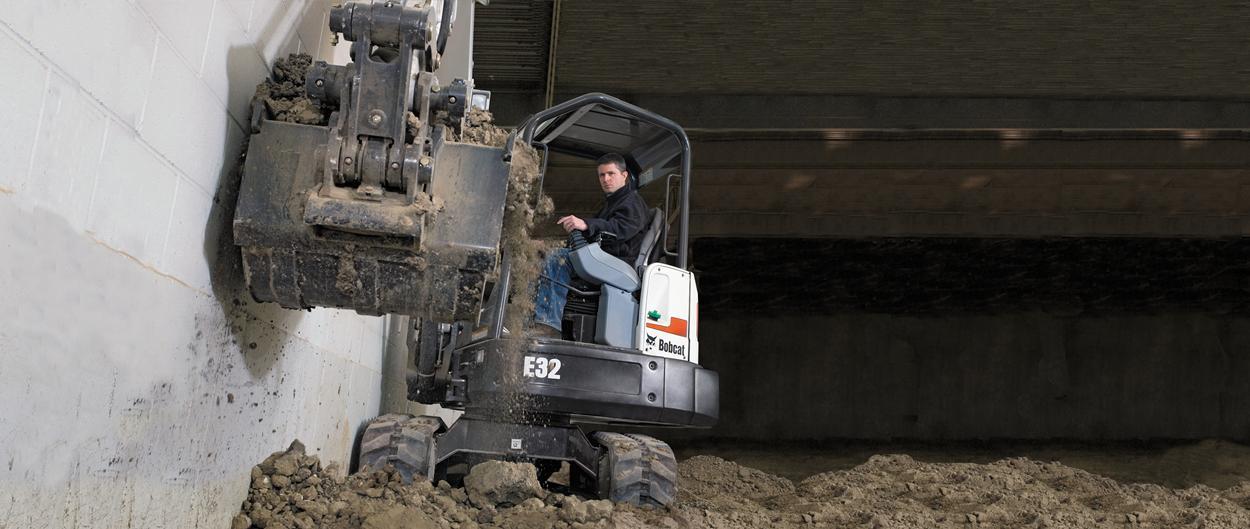 Bobcat E32 compact excavator (mini excavator) operates next to wall.