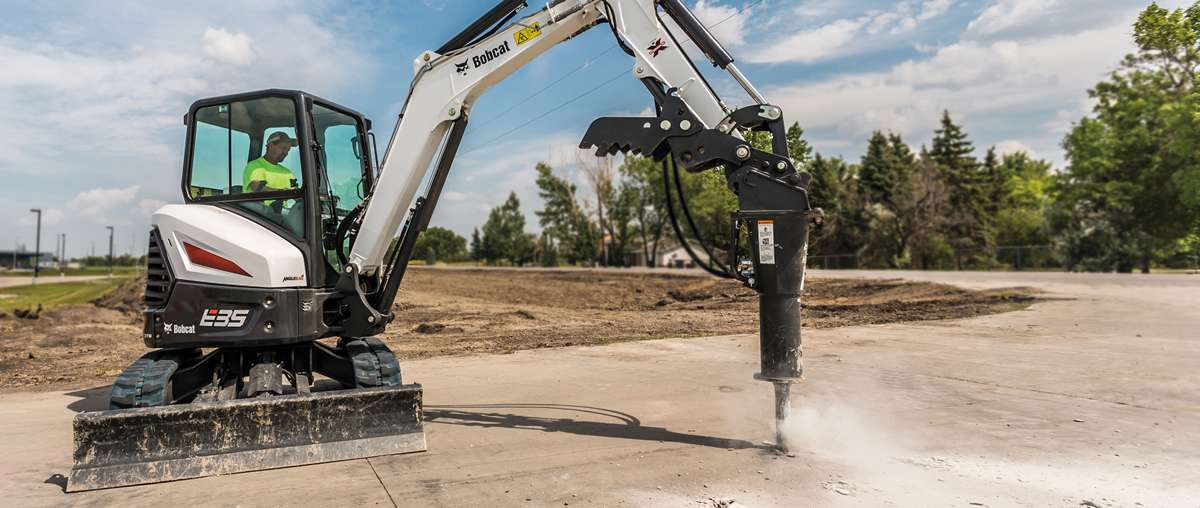 Compact Excavator Operator Uses Breaker Attachment to Impact Ground