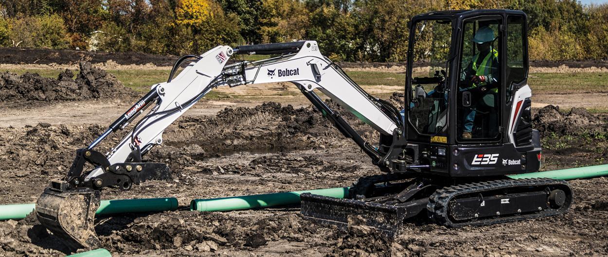 Compact Excavator Operator Piles Dirt Near a Hole