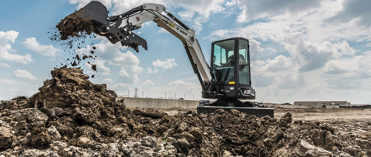 Bobcat E35 compact (mini) excavator piling dirt onto a pile with a bucket attachment.