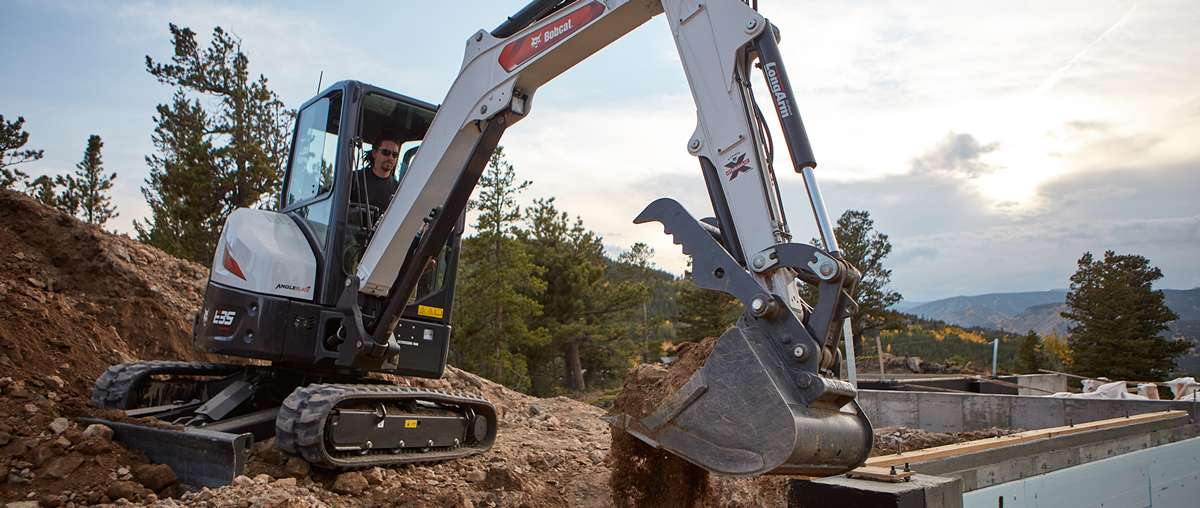 Operator digs near a foundation with an E35 and bucket attachment
