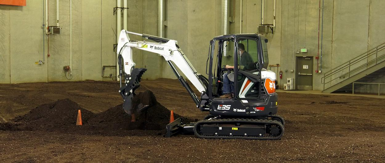 Bobcat E35 compact (mini) excavator moving dirt with a bucket attachment.