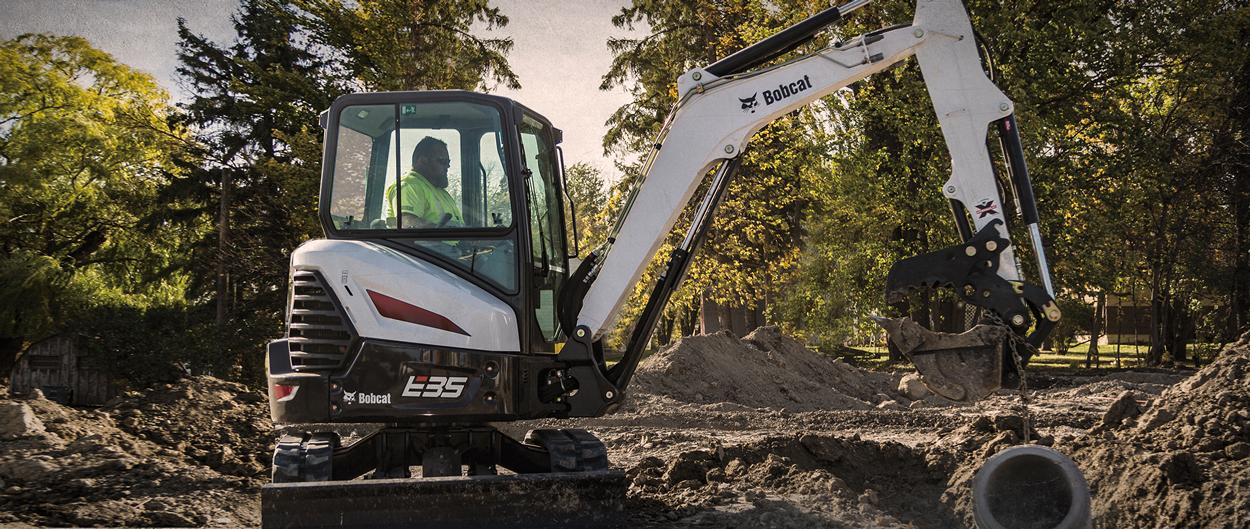 Bobcat E35 compact (mini) excavator and bucket attachment digging a hole for a culvert.