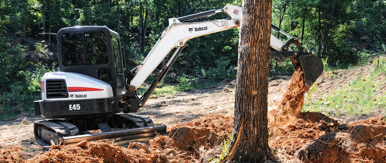 Bobcat E45 compact excavator (mini excavator) works near obstacles.