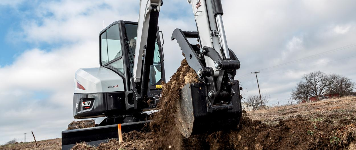 Landscaper Using Bobcat E50 Mini Excavator With Clamp Attachment To Dig A Trench