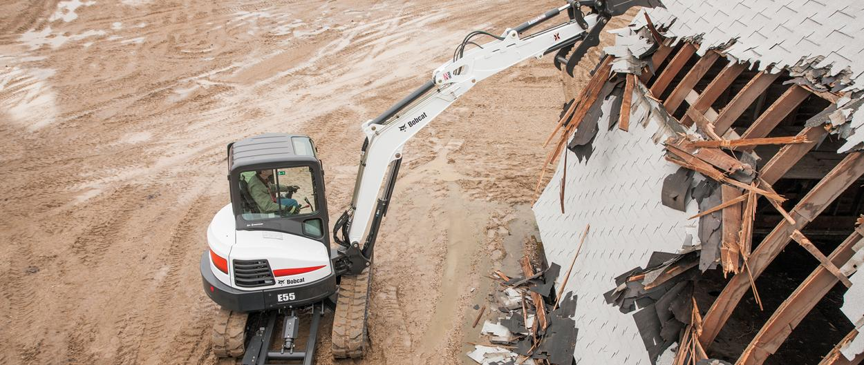 Bobcat E55 compact excavator (mini excavator) demolishes building.