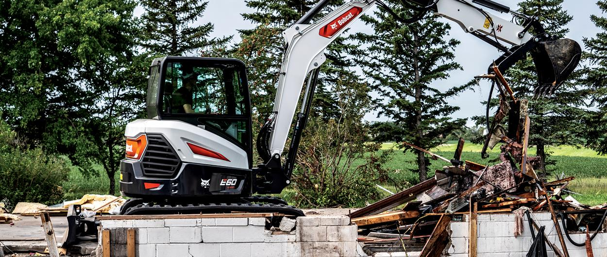 Operator Using Bobcat E60 Compact Excavator To Move Debris On Demolition Site